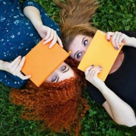 Two teen girls hiding behind books