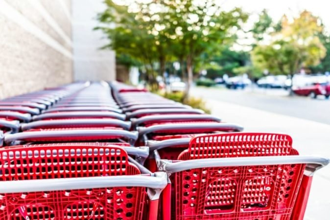 Red shopping carts lined up next to brick wall and near parking lot