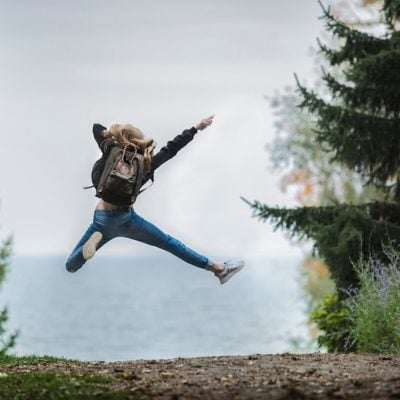 girl wearing backpack jumping