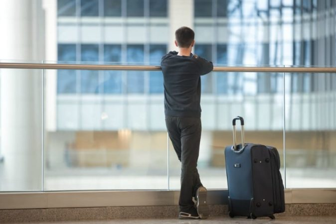 Teen boy with suitcase waiting for flight