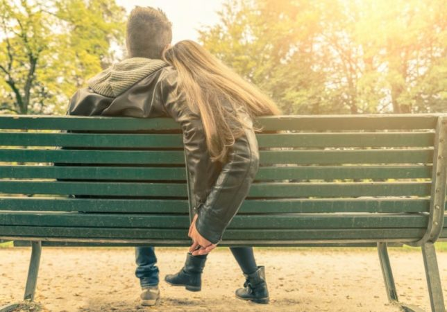 teen couple on park bench