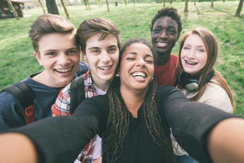 Multiracial high school freshman taking selfie