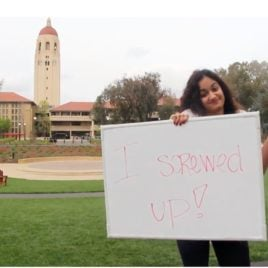 student holding sign at Stanford