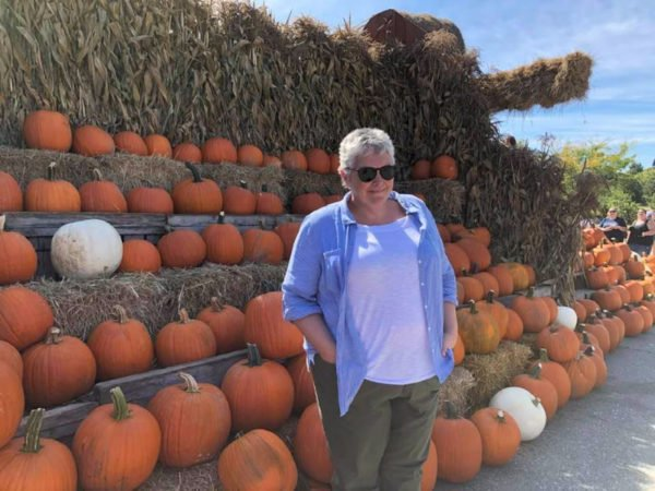 50 year old woman in front of pumpkin