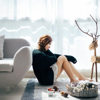 woman sitting against couch