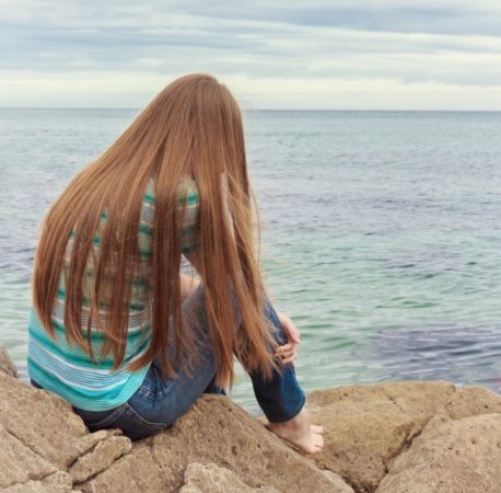 teen girl sitting by water