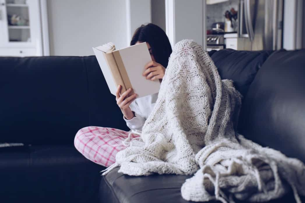 teen reading on couch