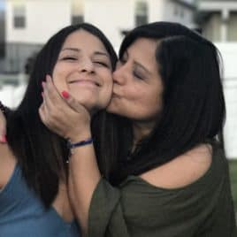 mom kissing teen daughter