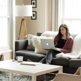 young adult woman working on couch