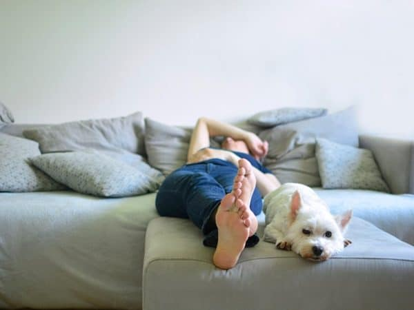 bored teen girl on couch with dog